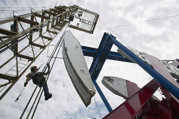 FILE - In this July 26, 2011, file photo, a worker hangs from an oil derrick outside of Williston, N.D. State data show that 1 billion barrels of oil have been produced from the rich Bakken shale formation in western North Dakota and eastern Montana. Data show that North Dakota has tallied 852 million barrels of Bakken crude, and Montana has produced about 151 million barrels. (AP Photo/Gregory Bull, File)