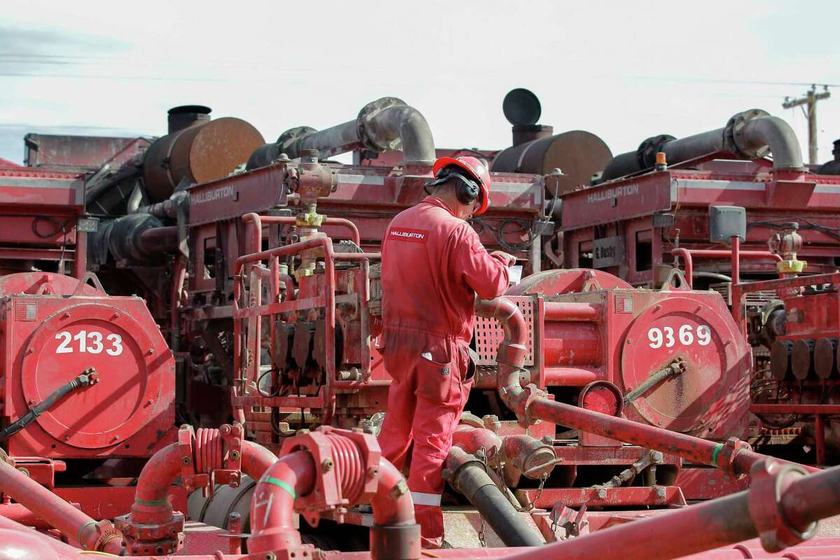 A Halliburton oil-field services employee works near rows of hydraulic fracturing pumping units.
