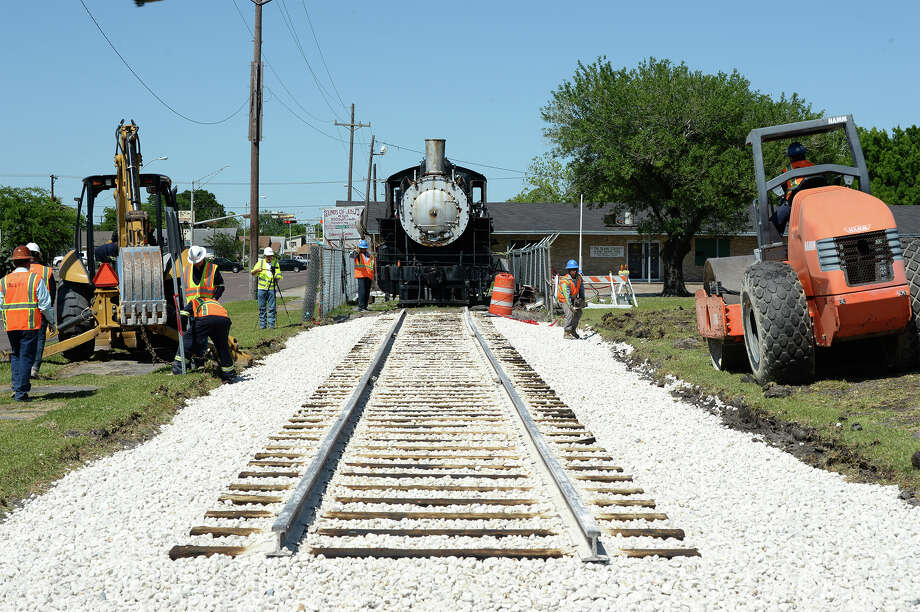 After building train tracks at Port Arthur's Bryan Park earlier this week, crews prepare a locomotive Thursday that will be moved today. Organizers plan to use a backhoe to pull the train. Photo: Guiseppe Barranco/The Enterprise, Photo Editor / Guiseppe Barranco ©