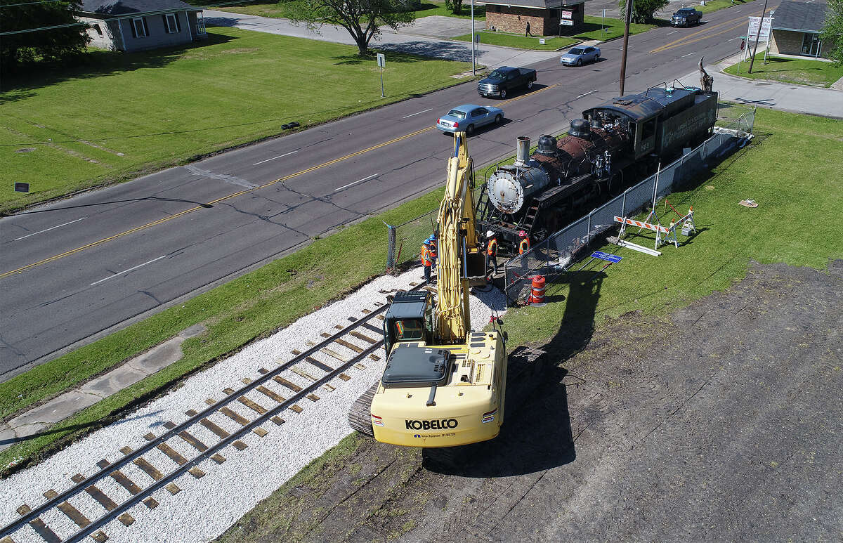After building train tracks at Port Arthur's Bryan Park earlier this week, crews prepare a locomotive Thursday that will be moved today. Organizers plan to use a backhoe to pull the train.