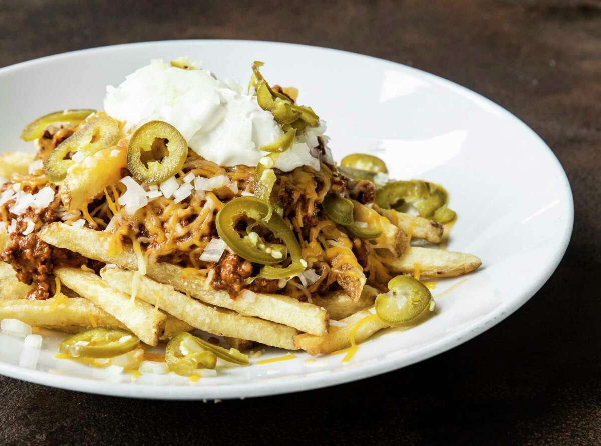 Chili cheese fries made with hand-cut fries, house-made chili, shredded cheddar, onion, pickled jalapeños and sour cream at The Hay Merchant.