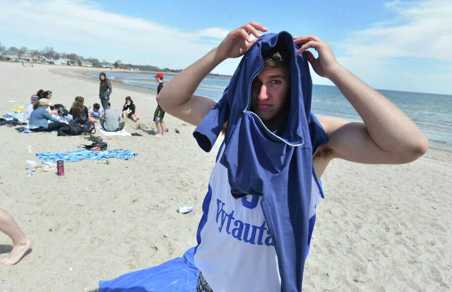 Charles Sagdiyev pulls on a hoodie after taking a swim with classmates from Wooster School in Danbury during a warm day at Compo Beach on Tuesday. The students were there for senior skip day. Photo: Alex Von Kleydorff / Hearst Connecticut Media / Norwalk Hour