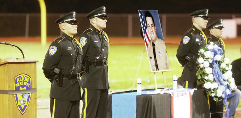 In this photo from October 2016, members of the Alton Police Honor Guard stand by a wreath they placed under a large photo of officer Blake Snyder, an Alton native and St. Louis County police officer, during a memorial ceremony at Alton's Public School Stadium. On Wednesday, Alton officials voted to name a road under construction after Snyder. Photo:       John Badman | The Telegraph