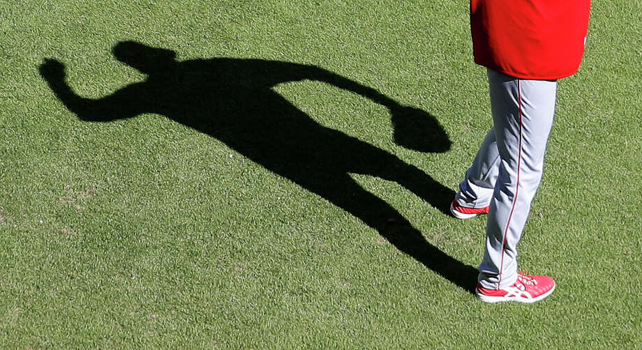 The 6-4 two-way phenom casts a long shadow as he tosses the ball in the outfield during Monday's pregame workouts. Photo: Karen Warren / © 2018 Houston Chronicle