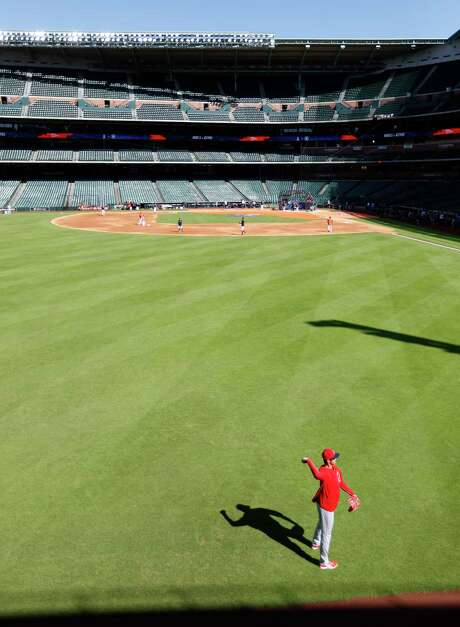 Just shy of the warning track in front of the Crawford Boxes, Shohei Ohtani lightly tosses the ball during Monday's batting practice as he prepares for his Houston debut the following night. Photo: Karen Warren / © 2018 Houston Chronicle