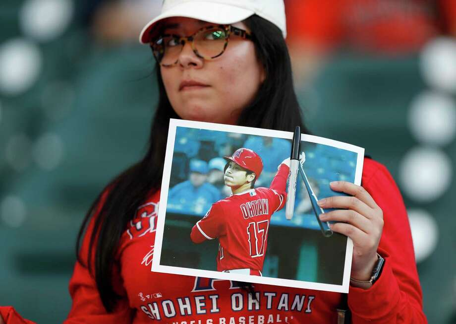 Gabby Solano of Houston holds a photo of Shohei Ohtani hoping to get it autographed before his start Tuesday. Photo: Karen Warren / © 2018 Houston Chronicle
