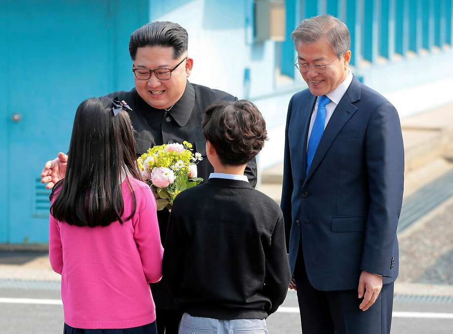 North Korean leader Kim Jong Un and South Korean President Moon Jae-in (right) are greeted by children bearing flowers. Photo: Korea Summit Press Pool