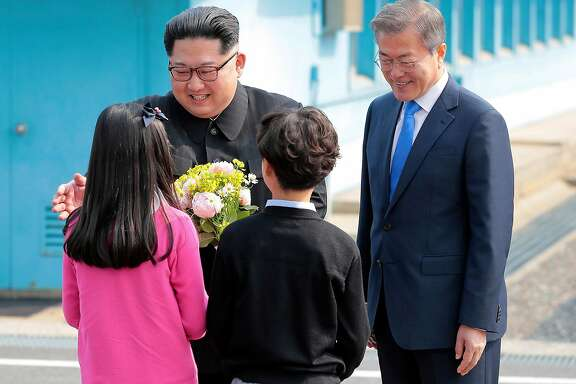 North Korean leader Kim Jong-un, left, and South Korean President Moon Jae-in, right, are greeted by children bearing flowers after Kim into South Korea in the border village of Panmunjom on Friday, April 27, 2018. Friday�s summit meeting between the leaders of North and South Korea was a master class in diplomatic stagecraft, with each scene arranged for its power as political theater and broadcast live. (Korea Summit Press Pool via The New York Times)  -- NO SALES; FOR EDITORIAL USE ONLY WITH NYT STORY KOREAS-TALKS-SCENE BY RUSSELL GOLDMAN FOR APRIL 28, 2018. ALL OTHER USE PROHIBITED. --