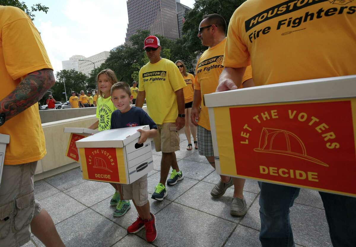 Madison, left, and Russell Blackmon, center, help Houston firefighters carry boxes, filled with more than 32,000 signatures to put equal pay on the ballot, over to the City Hall Annex building Monday, July 17, 2017, in Houston. ( Godofredo A. Vasquez / Houston Chronicle )