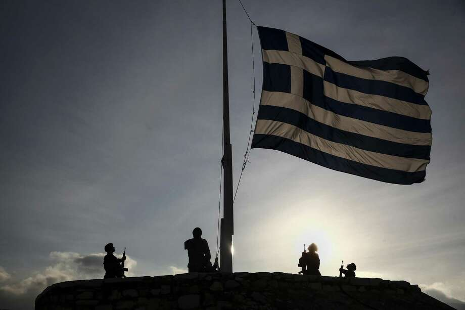Greek army soldiers stand to attention as they raise the national flag early morning on Acropolis Hill in Athens. Photo: Bloomberg Photo By Yorgos Karahalis / © 2017 Bloomberg Finance LP