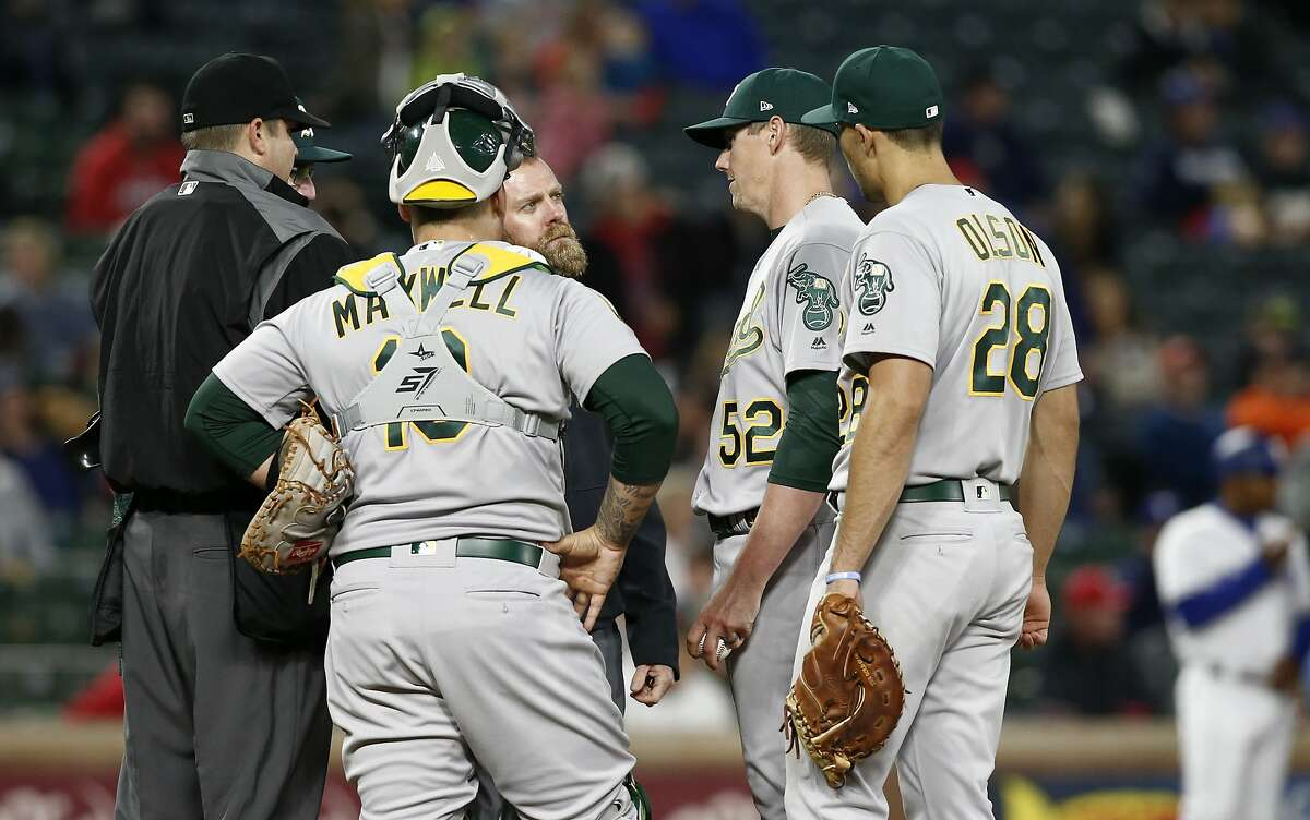 Oakland Athletics pitcher Ryan Buchter (52) talks with team personnel before being removed from the baseball game after just several pitches against the Texas Rangers, as catcher Bruce Maxwell (13) and first baseman Matt Olson (28) listen during the seventh inning of a baseball game Wednesday, April 25, 2018, in Arlington, Texas. (AP Photo/Mike Stone)