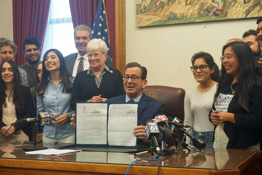 Gov. Dannel P. Malloy (center) signed into law on Friday April 27, 2018 a bill that opens financial aid at state universities to undocumented students brought into the country as children. He was joined by Lt. Gov. Nancy Wyman (center left) and undocumented student advocates. Photo: Emilie Munson