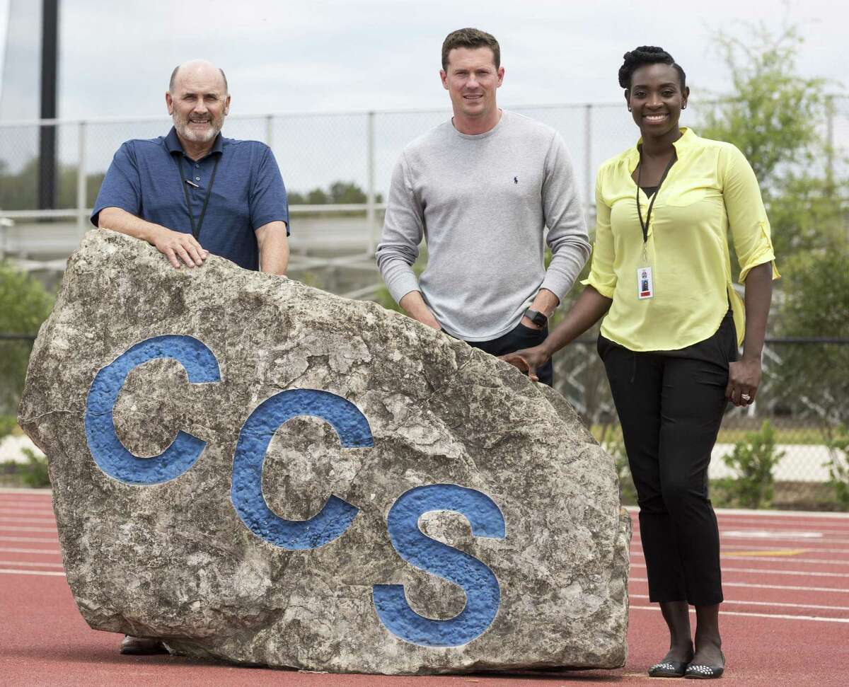 Cornerstone Christian School's new athletic hires Johnny Booty, left, football coach Abram Booty, center and girls basketball coach Sophia Young-Malcolm pose Wednesday, April 25, 2018 with the CCS rock moved from the school previous facility to the current location on NW Military Drive outside Loop 1604.
