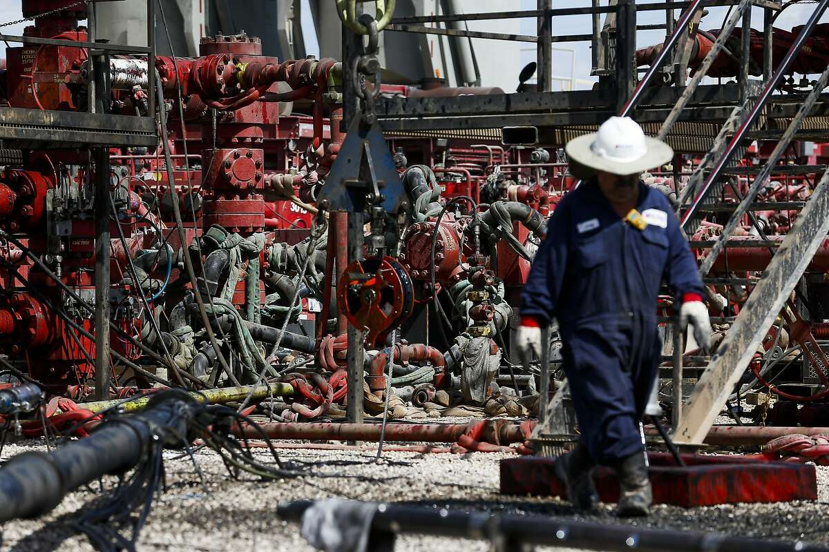 An employee walks by pressure pumps before hydraulic fracturing operations begin at a Chevron drilling site Wednesday, July 19, 2017 in Midland. NEXT: Photos of Big Oil's expansion into the Permian Basin.