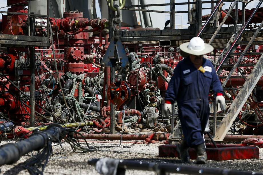 An employee walks by pressure pumps before hydraulic fracturing operations begin at a Chevron drilling site Wednesday, July 19, 2017 in Midland.  NEXT: Photos of Big Oil's expansion into the Permian Basin. Photo: Michael Ciaglo, Houston Chronicle