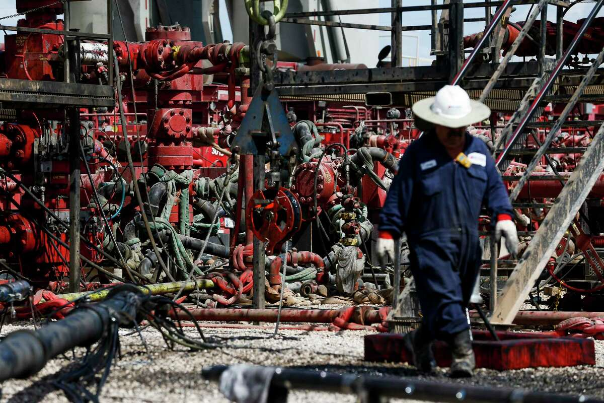 An employee walks by pressure pumps before hydraulic fracturing operations begin at a Chevron drilling in the Permian Basin.
