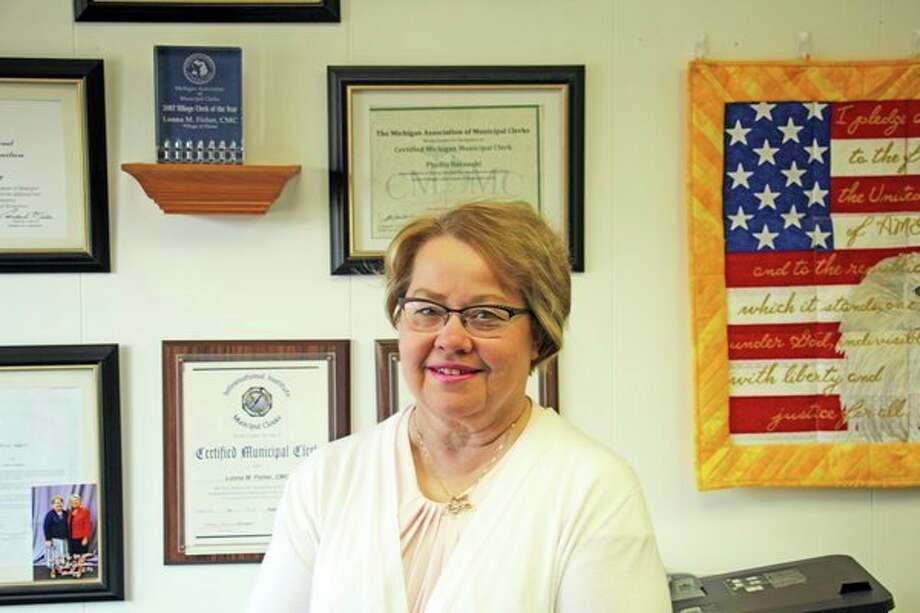 Lonna Fisher stands in front of the many accolades she achieved as clerk of the Village of Elkton, including the Michigan Association of Municipal Clerks Village Clerk of the Year award in 2007. She is retiring May 1 after 20 years on the job. (Seth Stapleton/Huron Daily Tribune)