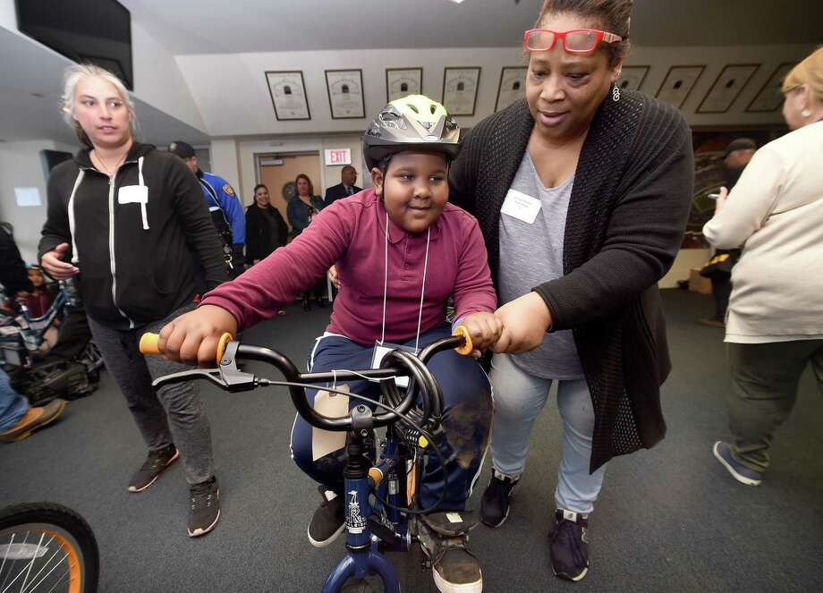 Mohammed Turay (center) of Quinnipiac Stem School gets some assistance trying out a new bicycle from Cheryl Brown in the Champions Room of Yale University's Kenney Center in New Haven on April 27, 2018. Brown was among teams of Yale University employees that assembled new bicycles as part of a team building project for students from Quinnipiac Stem School selected based on their kindness writing journal entries. Photo: Arnold Gold / Hearst Connecticut Media / New Haven Register