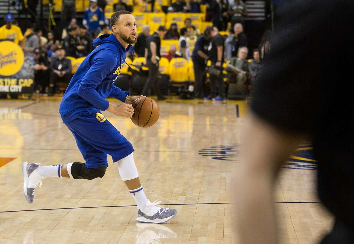 Warriors' Stephen Curry shoots around on the court during warm-ups while wearing a knee brace before the Golden State Warriors take on the San Antonio Spurs during the fifth game of the NBA Playoffs Round 1 at Oracle Arena Tuesday, April 24, 2018 in Oakland, Calif. Tuesday, April 24, 2018 in Oakland, Calif.