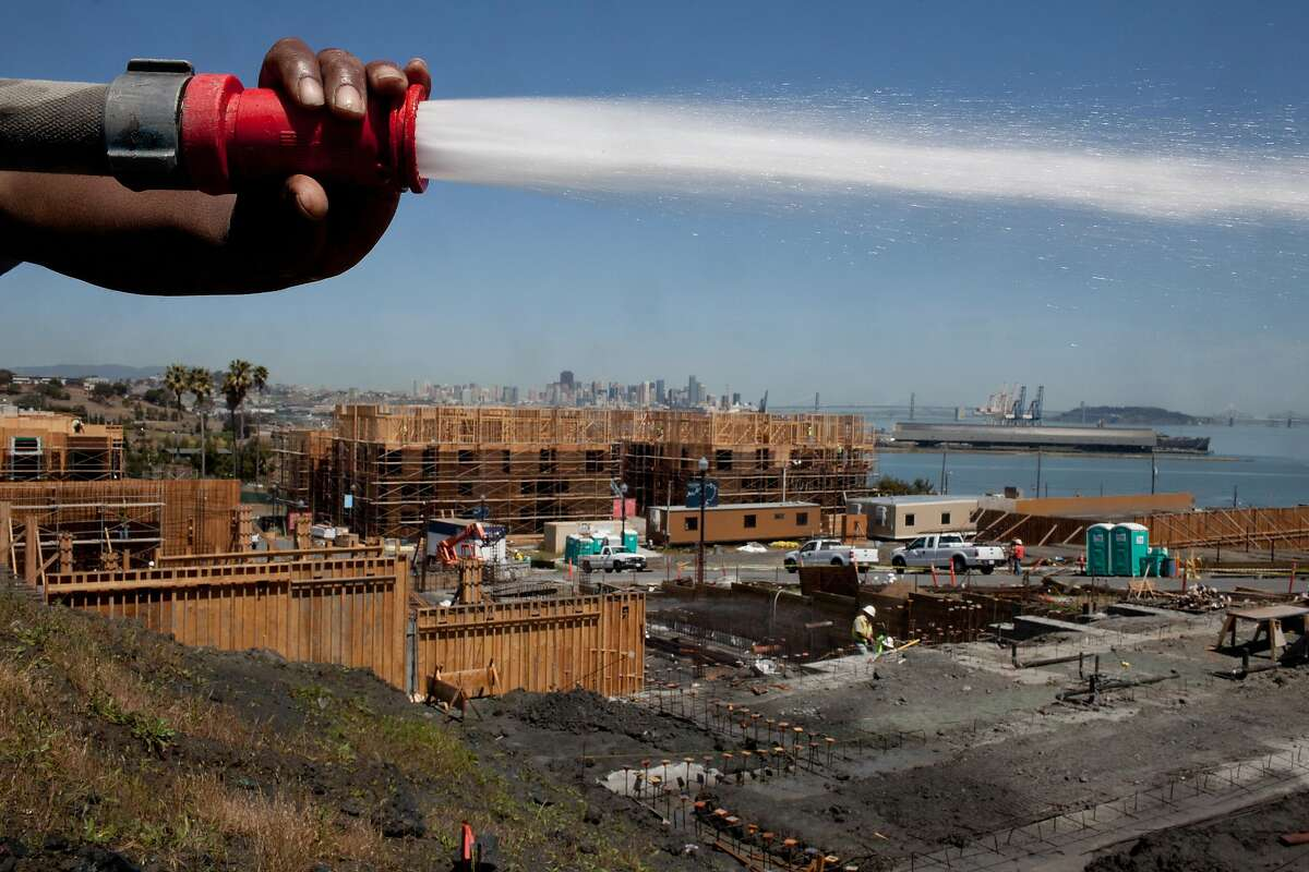 Michael Brown sprays down the land at the new development at the San Francisco Shipyard at Hunters Point in San Francisco, Calif. on Tuesday, May 13, 2014. These are the first homes hitting the market at the shipyard with 10,500 units.