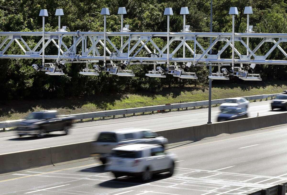 Cars pass under toll sensor gantries hanging over the Massachusetts Turnpike in Newton, Mass.
