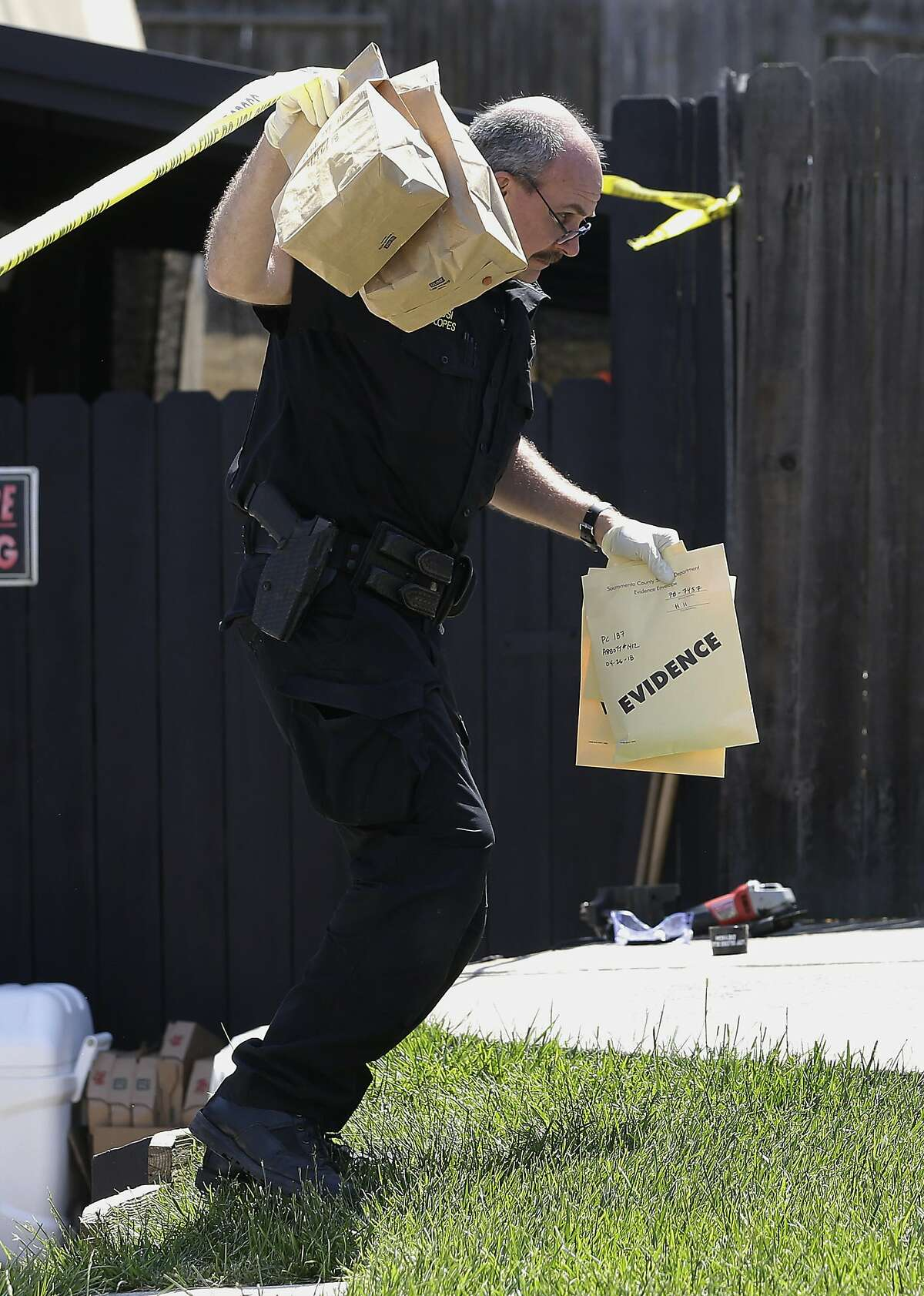 John Lopes, a crime scene investigator for the Sacramento Sheriff's office carries bags of evidence taken from the home of murder suspect Joseph DeAngelo to a sheriff's vehicle Thursday, April 26, 2018, in Citrus Heights, Calif. DeAngelo, 72, was taken into custody, Tuesday, on suspicion of committing multiple homicides and rapes in the 1970's and 1980's in California. Authorities spent the day going through the home for evidence. (AP Photo/Rich Pedroncelli)