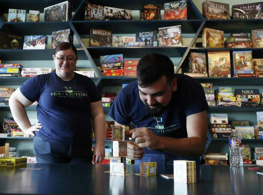 """""""Game Guides"""" Ryan Escontrias and Rachel Rentz play Rhino Hero at Houston's board game cafe, Tea + Victory, 2030 E. TC Jester, which is stocked with more than 500 board games and Game Guides, who are game experts there to help customers select and play games. It is also a restaurant with a a coffee and tea program, along with beer and wine, and a menu described as """"American classic meets English picnic."""" Photo: Karen Warren, Staff / Houston Chronicle / © 2018 Houston Chronicle"""