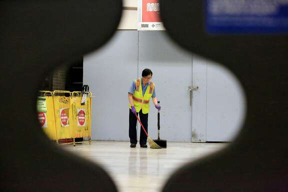 A worker is seen sweeping through the gates at a fare entrance in the Civic Center / UN Plaza Station on Friday, April 27, 2018 in San Francisco, Calif.