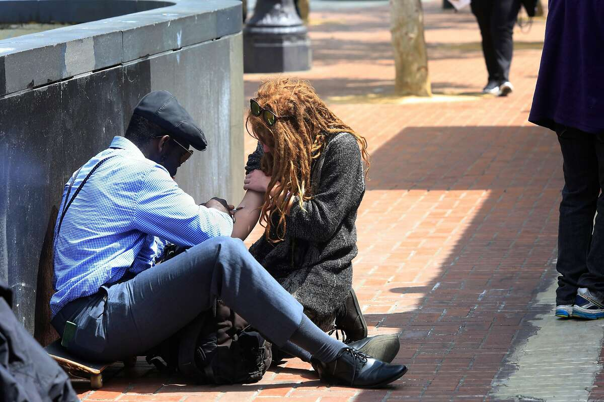 One person injects another with a needle on a syringe along Market Street outside an entrance to the Civic Center / UN Plaza Station on Friday, April 27, 2018 in San Francisco, Calif.
