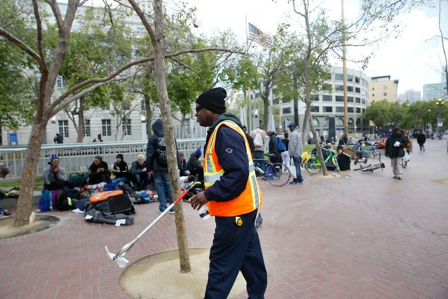Street sweeper Ivan Graddy picks up trash as he works his regular route at U.N Plaza. in San Francisco. Graddy says people will move from an area being cleaned but return when it's done. Photo: Lea Suzuki / The Chronicle
