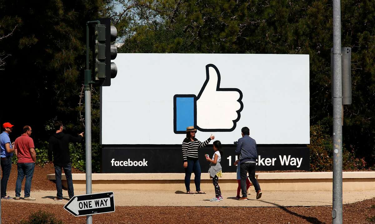 Visitors stop for photos at the Facebook sign in front of the company's Menlo Park headquarters. Facebook has reported that its median pay is $240,430.