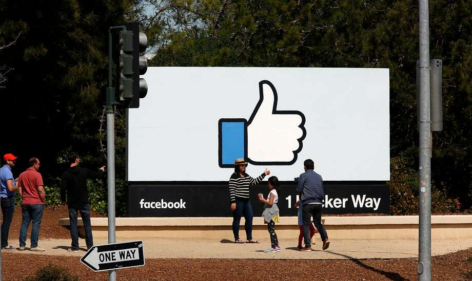 Visitors stop for photos at the Facebook sign in front of the Menlo Park headquarters. The company has reported that its median pay is $240,430. Photo: Michael Macor / The Chronicle