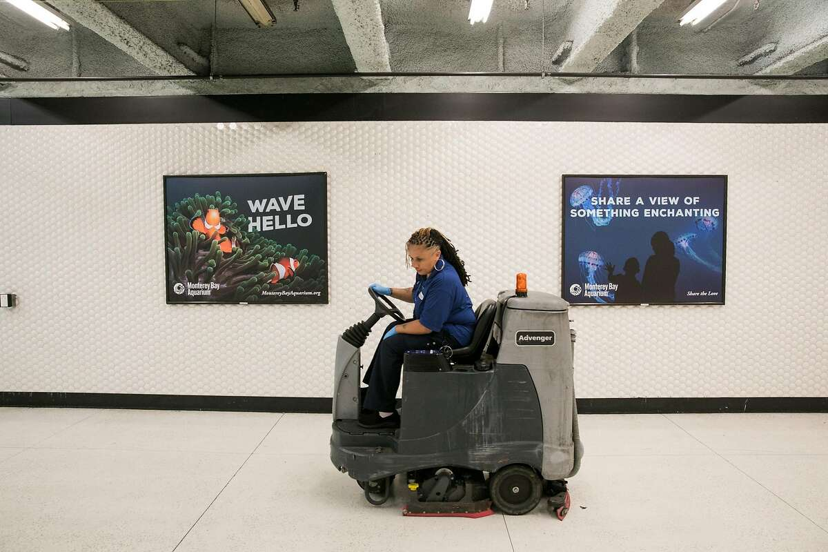 The BART custodian, Heather Oliver, cleans the floors of the Powell Street BART station in San Francisco, Calif. Thursday, July 13, 2017.