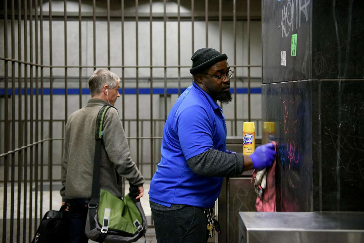 BART systems services member Dantone Sharkey cleans graffiti off of a wall in a stairwell at the Civic Center BART station in San Francisco, CA, on Friday February 9, 2018.