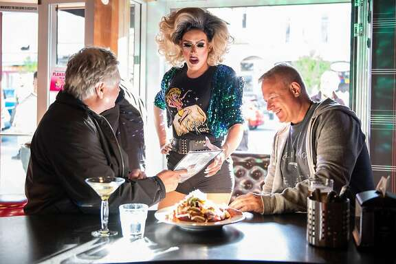 Carnie Asada, a �Mary� at Hamburger Mary�s in San Francisco, talks with customers on April 21, 2018. The restaurant, which started in SF in 1972, has become a national franchise, and recently returned to the city�s Castro neighborhood.