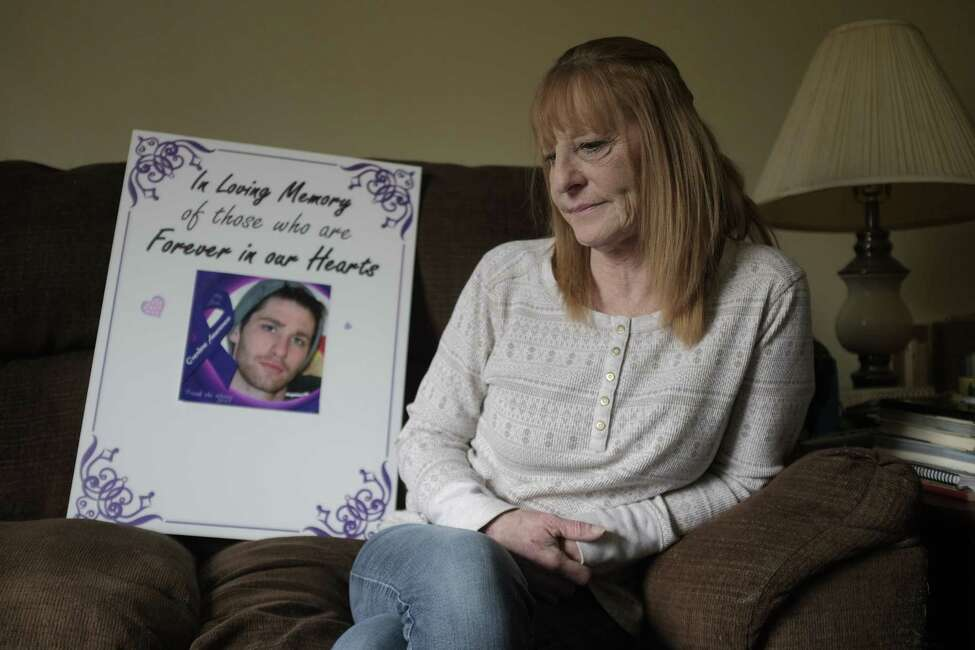 Julie Roy sits on her couch next to a poster she made with a photo of her son, William Timber, on it, seen here on Wednesday, April 18, 2018, in Poestenkill, N.Y. Timber dies of a drug overdose and Roy made the poster to carry at advocacy events and memorial walks. (Paul Buckowski/Times Union)