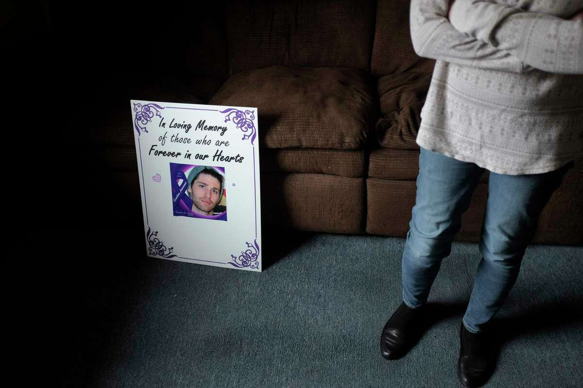 Julie Roy stands in her living room next to a poster she made with a photo of her son, William Timber, on it, seen here on Wednesday, April 18, 2018, in Poestenkill, N.Y. Timber dies of a drug overdose and Roy made the poster to carry at advocacy events and memorial walks. (Paul Buckowski/Times Union)