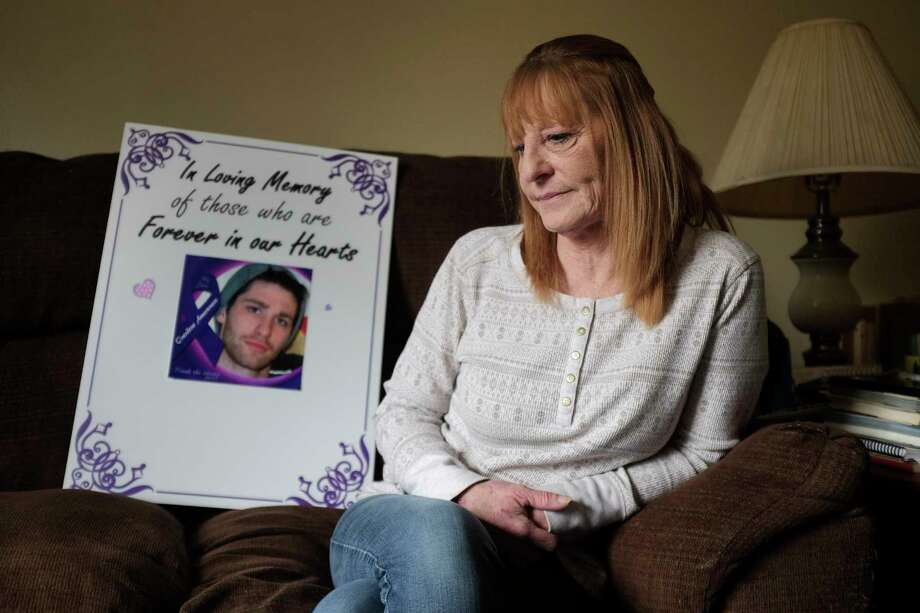 Julie Roy sits on her couch next to a poster she made with a photo of her son, William Timber, on it, seen here on Wednesday, April 18, 2018, in Poestenkill, N.Y. Timber dies of a drug overdose and Roy made the poster to carry at advocacy events and memorial walks. (Paul Buckowski/Times Union) Photo: PAUL BUCKOWSKI / (Paul Buckowski/Times Union)