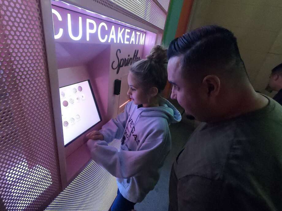 Jadyn Morin, 11, considers the options while father Rick looks on at a cupcake ATM outside Sprinkles cupcake shop, an example of the high-tech wizardry popular in Sin City. Photo: Spud Hilton / The Chronicle