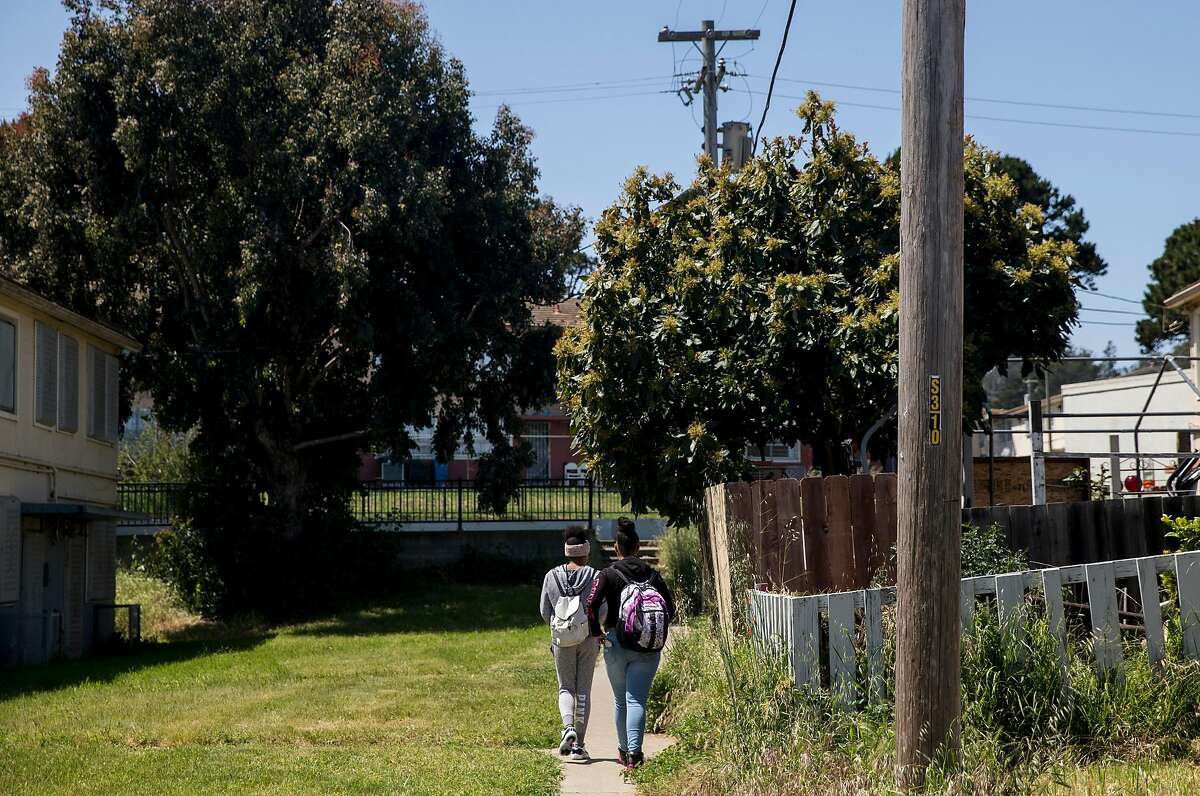 Two teens walk home from school through the Sunnydale Housing Project Wednesday, April 25, 2018 in the Sunnydale neighborhood of San Francisco, Calif.