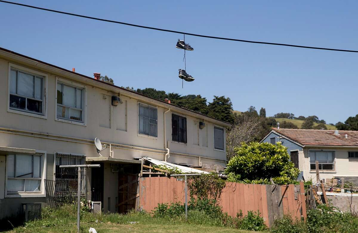 A pair of sneakers hangs on a power line above a row of public housing units Wednesday, April 25, 2018 in the Sunnydale neighborhood of San Francisco, Calif.