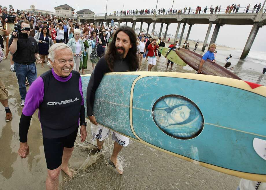 The Rev. Christian Mondor (left) and the Rev. Matt Munoz head to the surf in Huntington Beach in 2010. Photo: Richard Vogel / Associated Press 2010