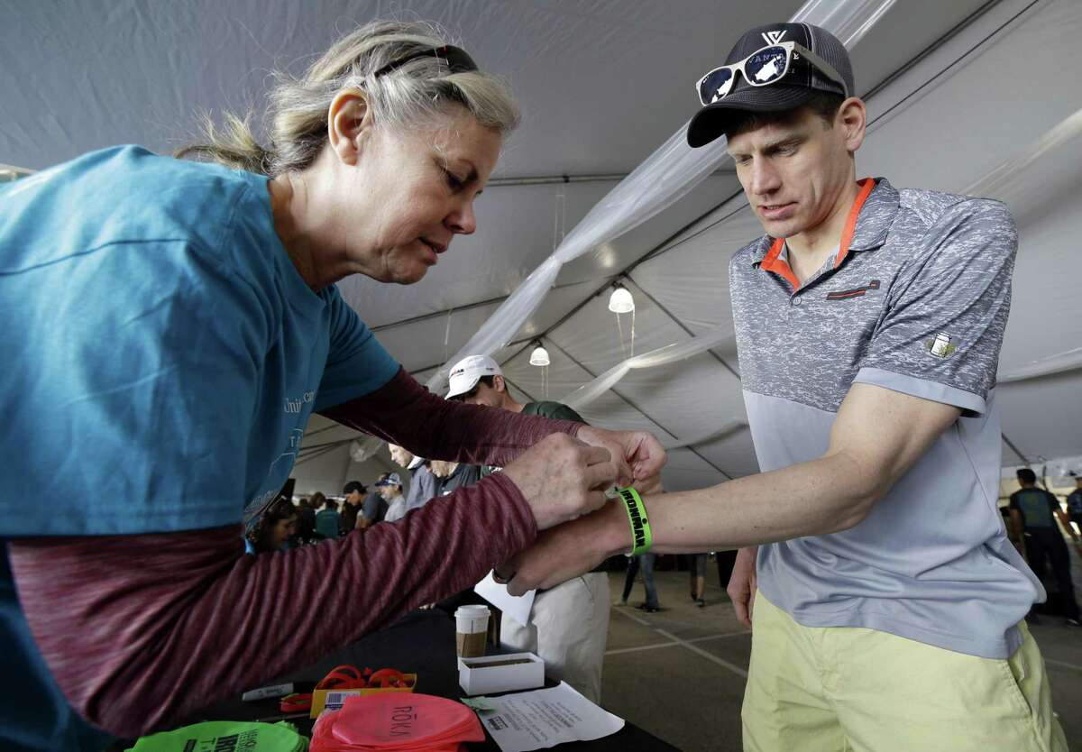 Volunteer Lea Brown (left) puts a wrist band on athlete Scott Hansen of New York during check in day Thursday, April 26, 2018, for the Memorial Hermann Ironman North American Championship Thursday, April 26, 2018, in The Woodlands, TX. The event will be held Saturday April 28, 2018. (Michael Wyke / For the Chronicle)