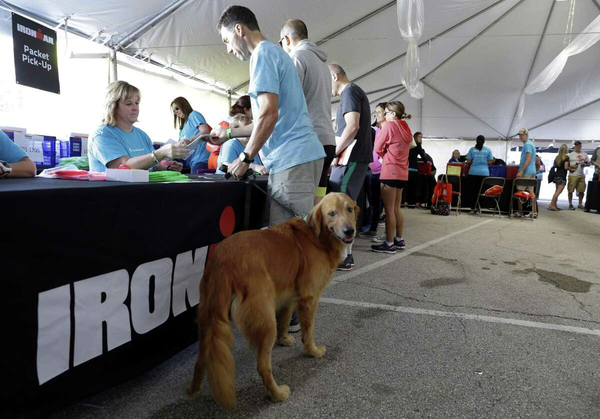 Dave Burger and his dog Dax get caps, numbers and wristbands during check in day Thursday, April 26, 2018, for the Memorial Hermann Ironman North American Championship Thursday, April 26, 2018, in The Woodlands, TX. The event will be held Saturday April 28, 2018. (Michael Wyke / For the Chronicle)