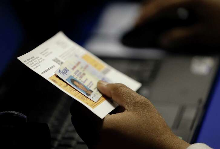 """An election official checks a voter's photo identification at an early voting polling site in Austin. In a split ruling released late Friday, a three-judge panel said opponents of the revised voter ID requirements in Texas failed to prove fixes the Legislature made to its original voter ID law still had a """"discriminatory effect on indigent minority voters."""""""
