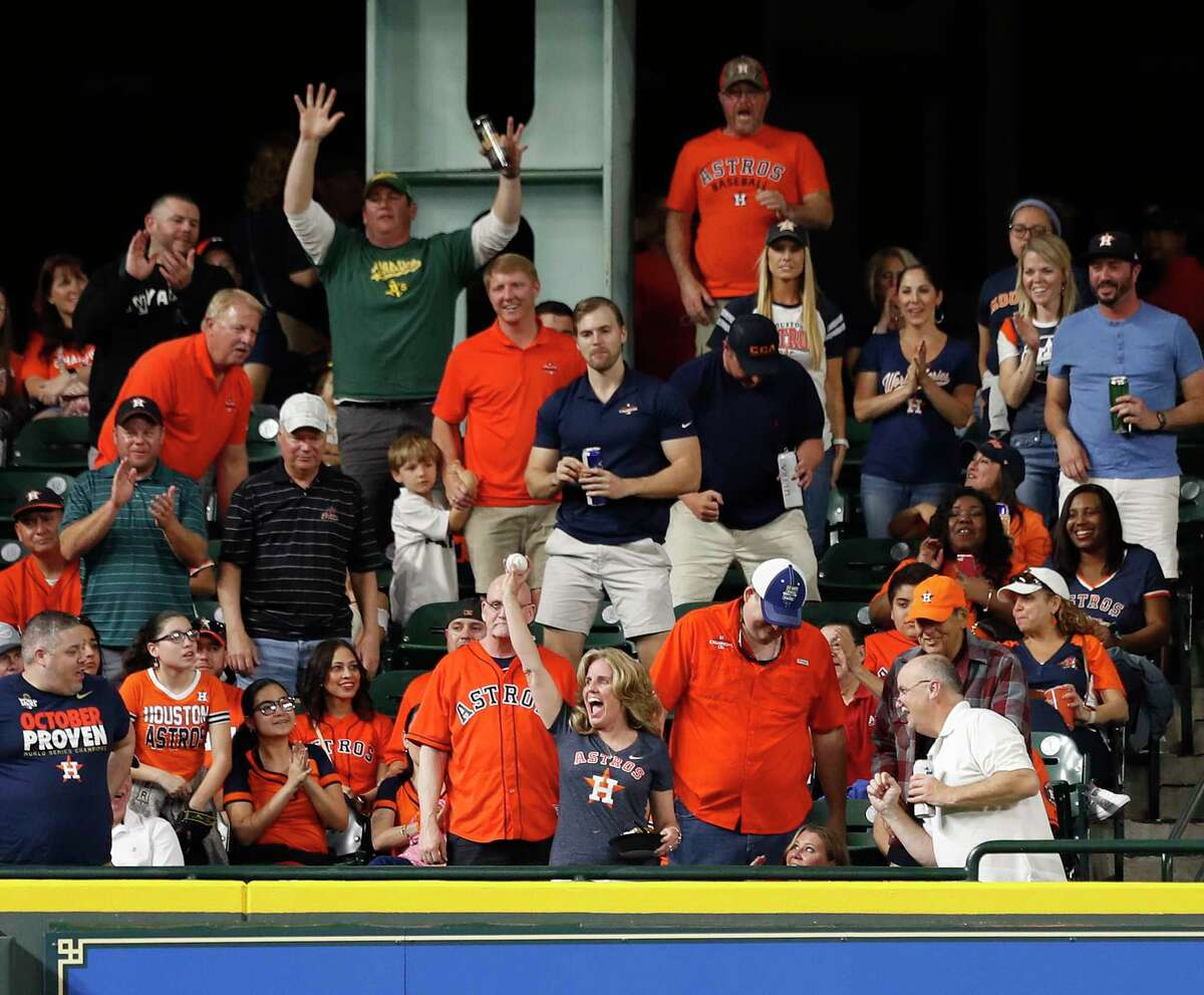 A woman in the Crawford Boxes holds Oakland Athletics third baseman Matt Chapman's home run ball during the fifth inning of an MLB game at Minute Maid Park, Friday, April 27, 2018, in Houston.