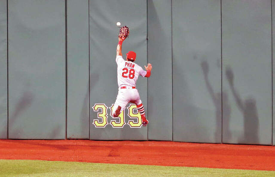 Cardinals center fielder Tommy Pham leaps as he tries to catch a ball hit by the Pirates' Jordy Mercer that went for a two-run triple in the ninth inning of Friday night's game in Pittsburgh. Photo:       AP