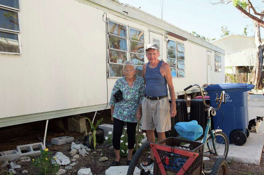 Terry and Sharon Baron stand for a photograph in front of the mobile home they lost during Hurricane Irma in Big Pine Key, Florida, on April 17, 2018. Photo: Bloomberg Photo By Alicia Vera. / © 2018 Bloomberg Finance LP