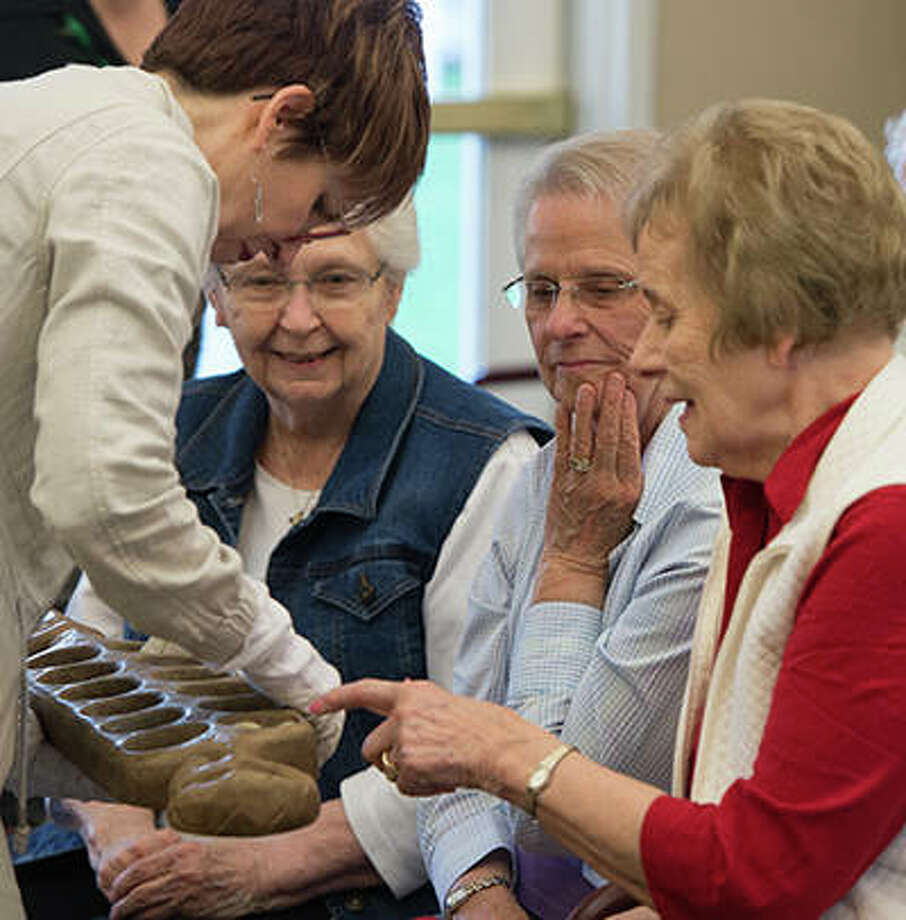 University Museum Collections Manager Erin Vigneau-Dimick shows Meridian Village residents artifacts from its collection. The featured residents include Dorothy Kueper, Joan Meier and Alice Mueller. Photo:       For The Telegraph