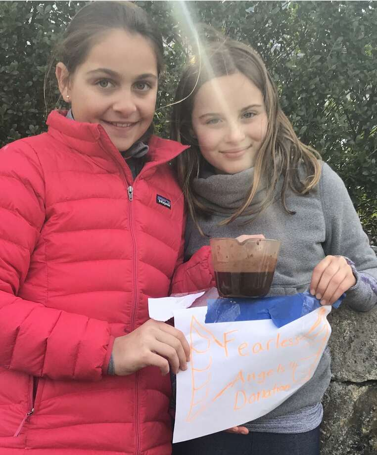 Lulu Ploog and Ansley Bieger of Belle Haven work at their cocoa and coffee stand earlier this month. The money fourth-graders raised was donated to the Fearless Angels Foundation to help provide a scholarship for aquatic therapy to an autistic child. Photo: Contributed /